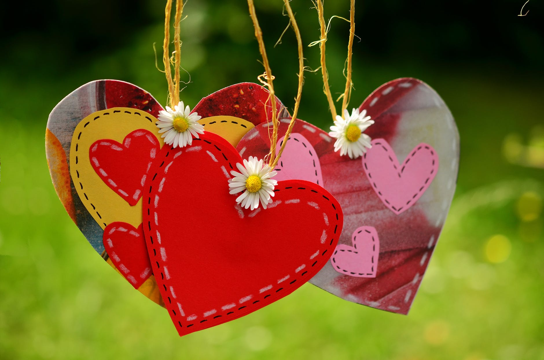 three red hearts hanging with white flowers